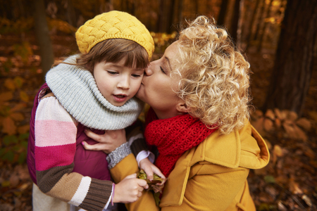 Mother giving a kiss girl on cheek Stock Photo