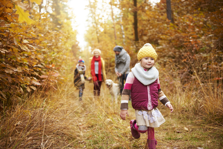 Walking girl and family in the background Stock Photo