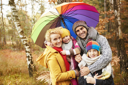 Family looking for shelter with umbrella