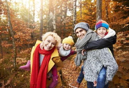 숲에서 놀고있는 아이들과 함께있는 부모 스톡 콘텐츠