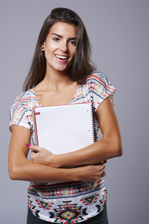 Paper notebook in hands of beautiful woman photo