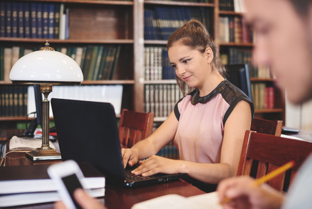 Woman using laptop in library Stock Photo