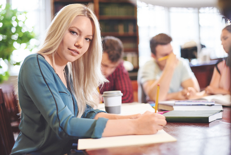 post secondary schools: Woman studying in library with another students Stock Photo