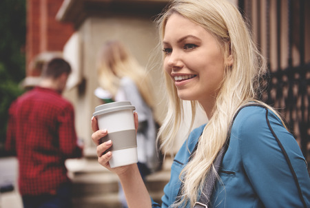 post secondary schools: Female student holding hot coffee Stock Photo