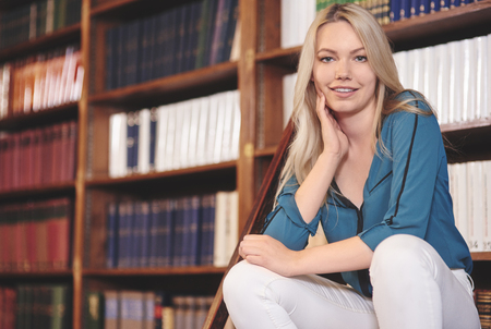 Pretty student relaxing in library Stock Photo