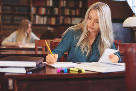 post secondary schools: Female student at work in library