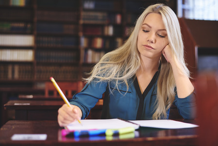 post secondary schools: Young woman learning in library Stock Photo