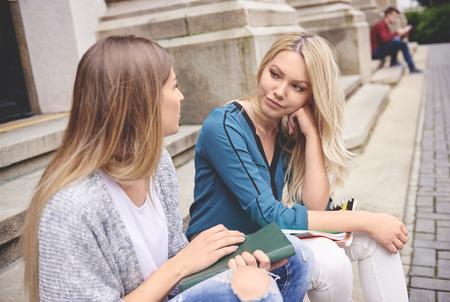 Twee vrouwelijke studenten zitten en praten Stockfoto - 83611436