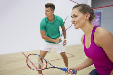 Focused man and woman playing squash together