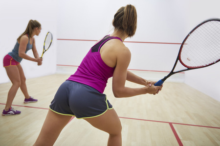 Women playing racket sport indoors
