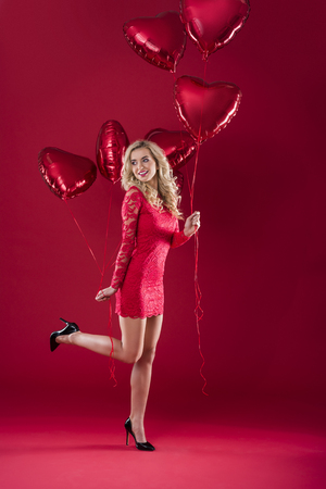 Woman with two bunches of heartshape balloons
