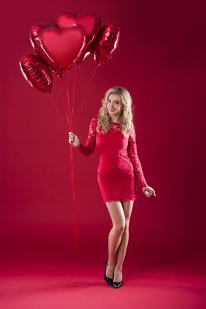 Smiling blonde holding big bunch of red balloons