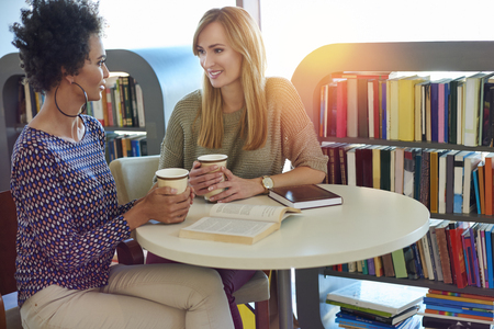 Two best friends drinking coffee over good books Фото со стока