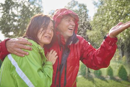 Senior couple embracing in rain