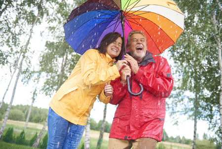 Wet couple hiding under colorful umbrella