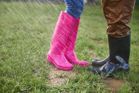 Mann und Frau in den Gummistiefeln draußen am regnerischen Tag Standard-Bild - 84204799