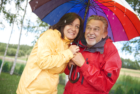 Senior couple sharing an umbrella in the rain