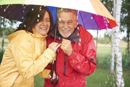 Couple of friend hiding under umbrella Imagens