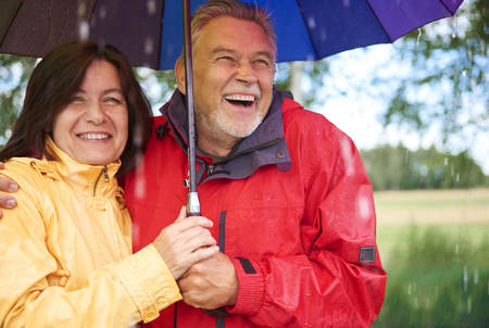 Happy senior couple standing during rain Imagens