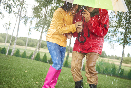 Senior couple standing together under an umbrella in the rain