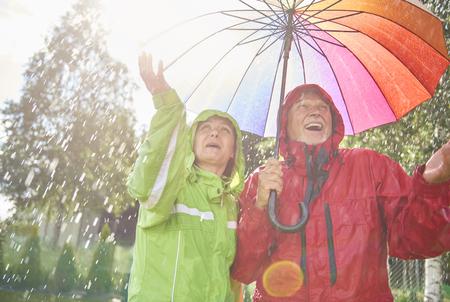 Senior couple playing with rain Stock Photo