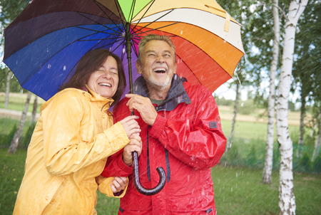 Couple looking for shelter with umbrella