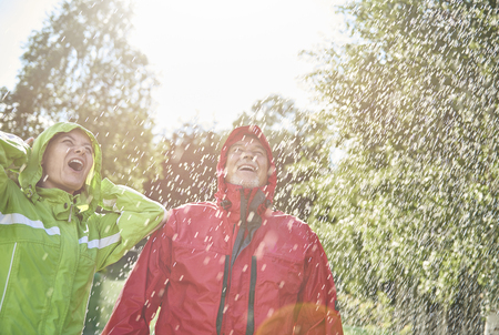 Exhilarated couple standing in rain Stock Photo