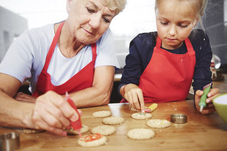 Grandmother with girl decorating christmas cookies Stock Photo