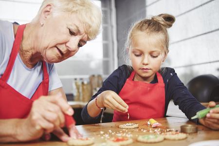 クッキーにアイシングを適用する女の子とおばあちゃん 写真素材