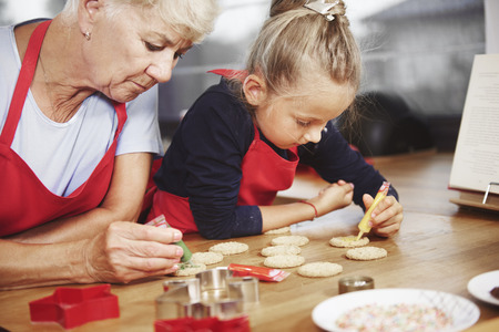 Small girl decorating cookies with her grandma