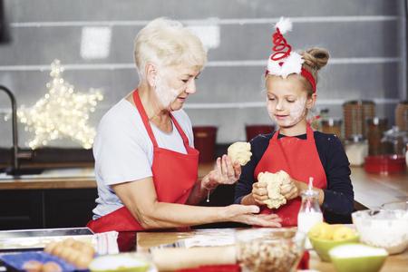Senior con chica amasando la masa en la cocina Foto de archivo - 84317526