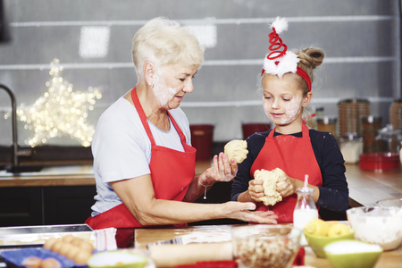 Senior with girl kneading dough in kitchen Stock Photo