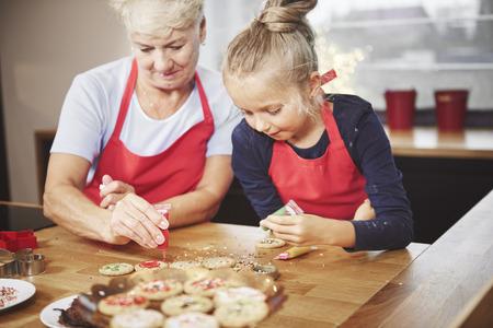 アイシングでクッキーを飾るおばあちゃんと孫