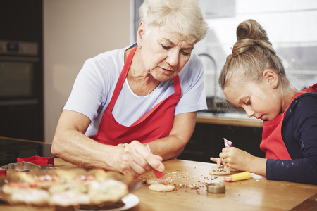 Grandma with girl baking and decorating cookies together Stock Photo