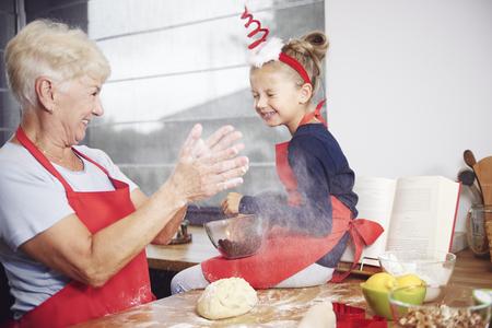 Grandmother and granddaughter enjoying in kitchen Foto de archivo