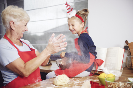 Grandmother and granddaughter enjoying in kitchen Standard-Bild