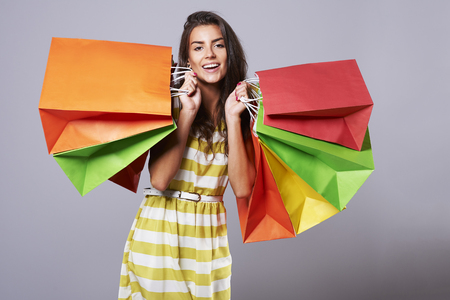 Positive emotions of woman with colorful shopping bags