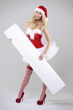 Long white placard held by sexy santa