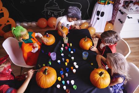 Kids painting a pumpkin for halloween