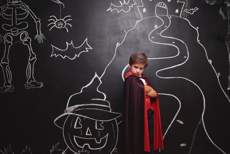 Boy in vampire costume posing