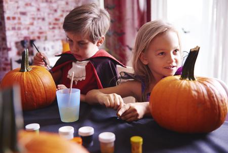Siblings painting a pumpkin at home