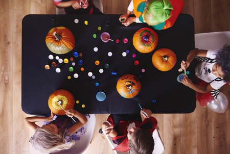 View from above kids painting pumpkins Stock Photo