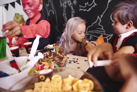 Children sharing food at halloween party Stock Photo
