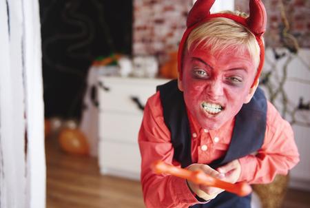 Jongen in duivelskostuum die mensen proberen te doen schrikken