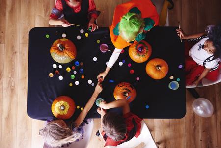Kids in costume decorating a pumpkin Stock Photo