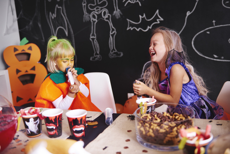 Cheerful girls taking a treat at halloween party