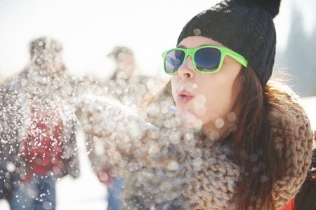 woman blowing the snow in front of camera