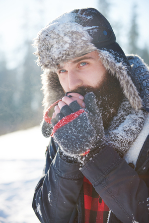 Frozen hands of man with beard