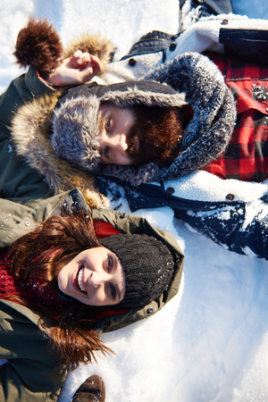 Couple lying on the white snow