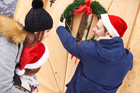 Man hanging the Christmas wreath on the door Stock Photo